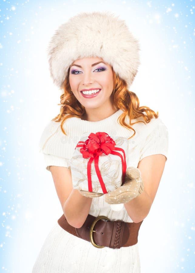 Femme dans des vêtements d'hiver tenant un présent photographie stock libre de droits