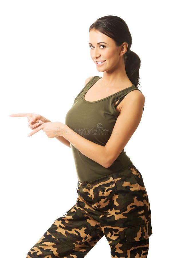Femme dans des vêtements militaires indiquant la gauche images stock
