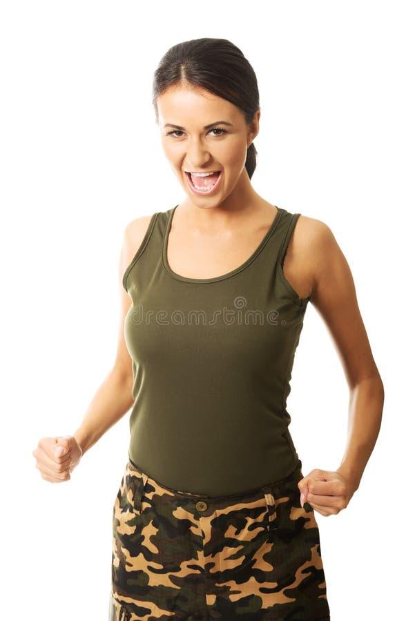 Femme dans des vêtements militaires montrant son agressivity des cris et en faisant des poings photos libres de droits
