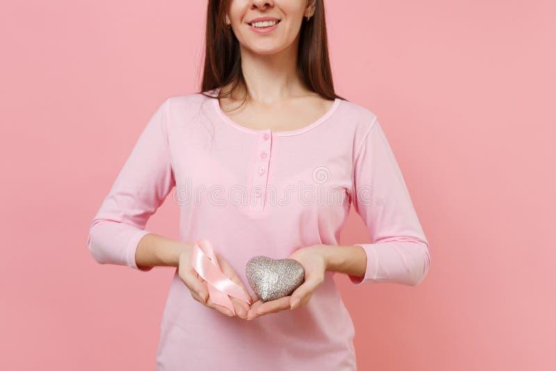 Femme dans des vêtements roses tenir à disposition le ruban en soie rose sur le fond en pastel de mur, portrait de studio médical image stock