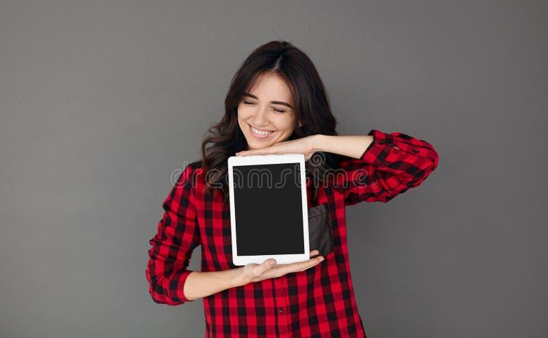 Femme dans l'écran de tablette occasionnel rouge de blanc de showig de chemise photo libre de droits
