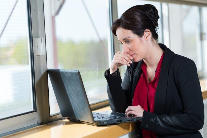 Femme dans l'?quipement de bureau regardant l'ordinateur portable images libres de droits