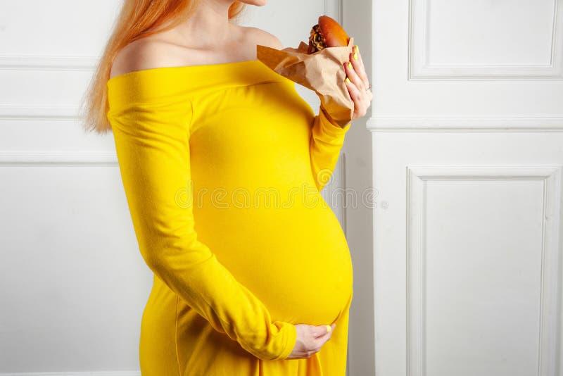 Femme dans l'état de grossesse appréciant mangeant son hamburger dans l'enveloppe de papier images libres de droits