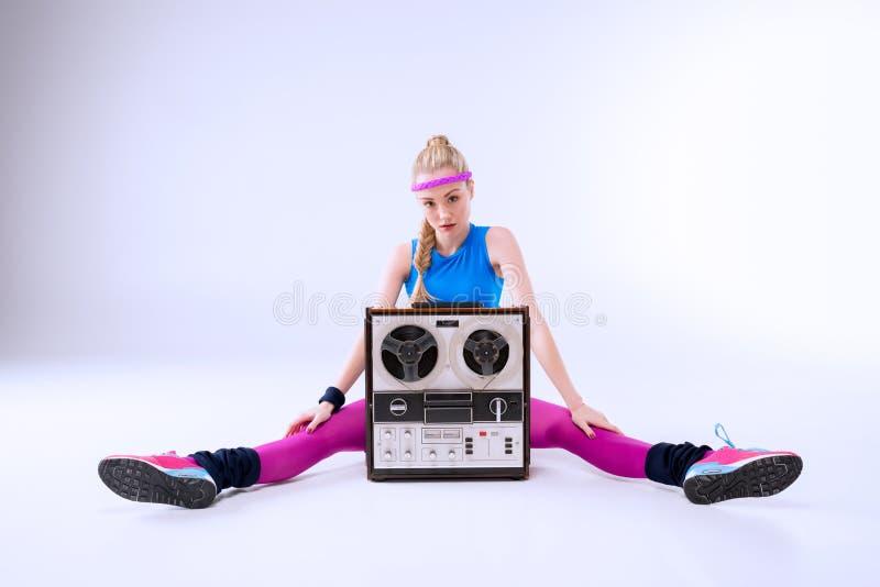 Femme dans l'habillement de forme physique se reposant près du rétro tourne-disque photographie stock