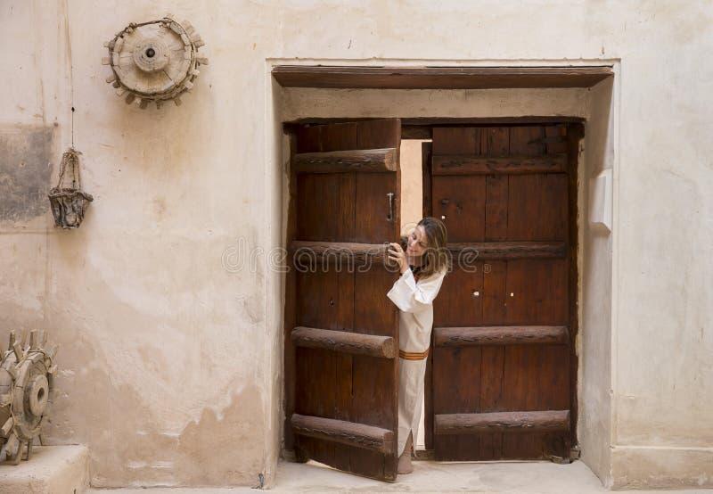 Femme dans l'habillement traditionnel semblant porte traversante et vieille dedans images stock