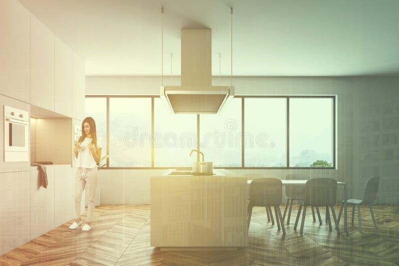 Femme dans l'intérieur blanc de cuisine avec une table images libres de droits
