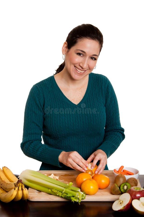 Femme dans l'orange d'écaillement de cuisine images stock