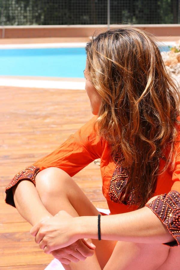 Femme dans l'orange par le regroupement image stock