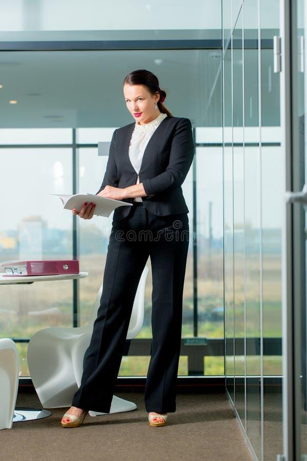 Femme dans l'?quipement formel dans le bureau en verre photos stock