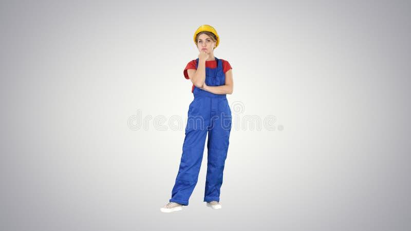 Femme dans l'uniforme de construction écoutant des instructions sur le fond de gradient photographie stock libre de droits