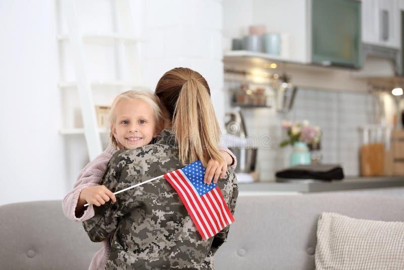 Femme dans l'uniforme militaire avec sa petite fille images stock