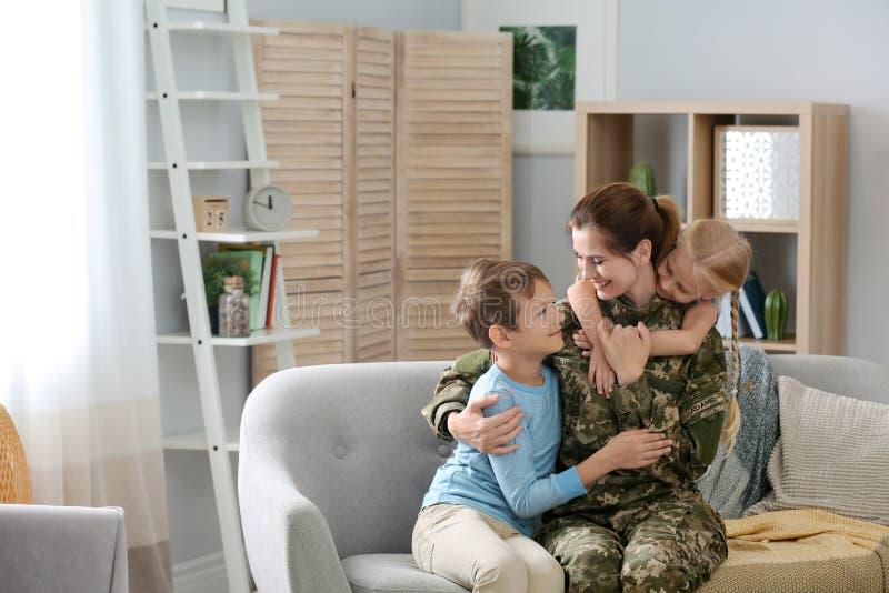 Femme dans l'uniforme militaire avec ses enfants sur le sofa photographie stock