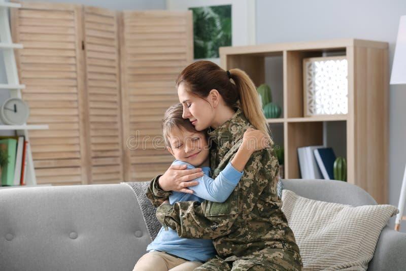 Femme dans l'uniforme militaire avec son petit fils sur le sof images libres de droits