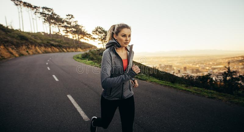 Femme dans l'usage de forme physique fonctionnant sur une rue vide pendant le matin Femme de forme physique pulsant sur une route photo stock