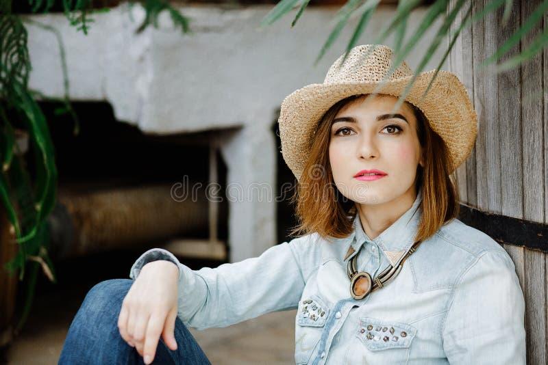 Femme dans l'usage occidental dans le chapeau de cowboy, les jeans et des bottes de cowboy images stock