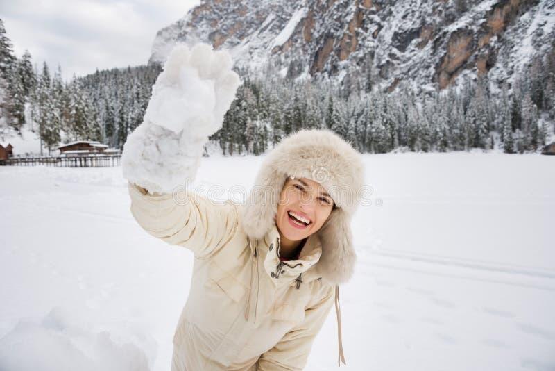 Femme dans la boule de neige de lancement blanche de chapeau de manteau et de fourrure dehors image stock