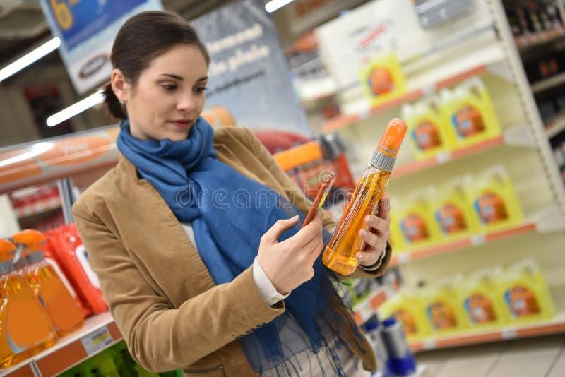 Femme dans la boutique de voiture choisissant des produits photos libres de droits