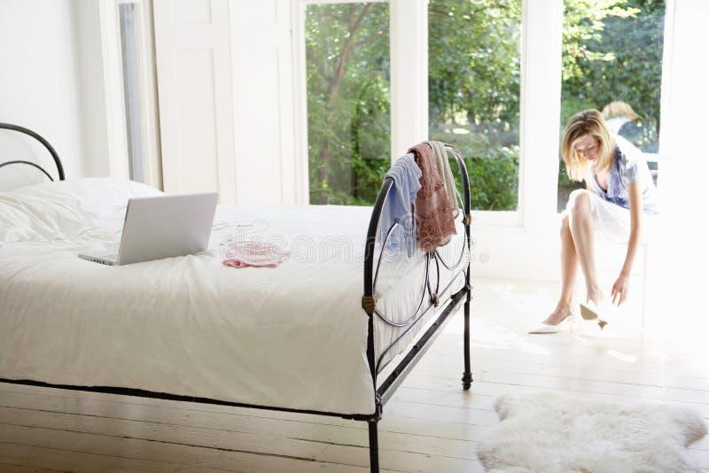 Femme dans la chambre à coucher mettant sur des chaussures photo stock