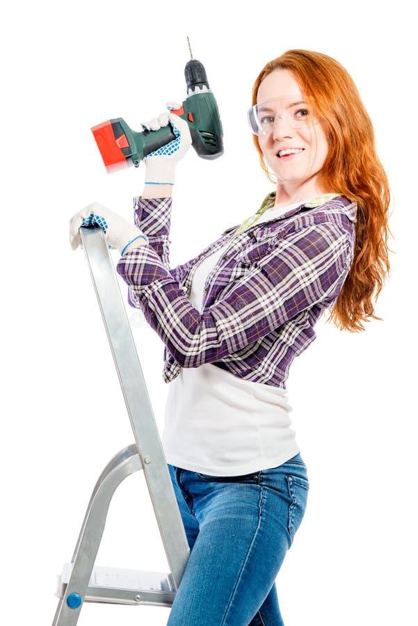 femme dans la chemise de plaid sur l'escabeau avec l'outil d'isolement sur b blanc image stock