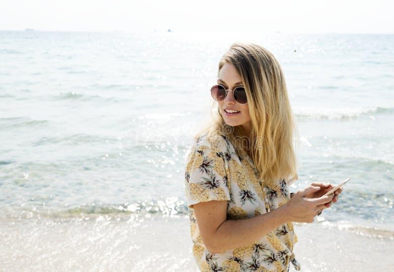 Femme dans la chemise florale jaune et blanche noire de bouton- tenant l'aviateur de port Sunglasses Near Body de Smartphone de l photographie stock