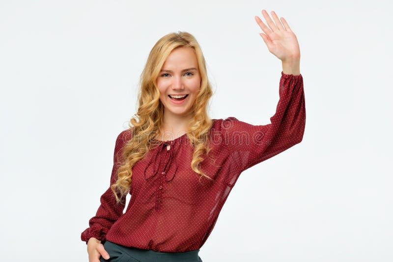 Femme dans la chemise rouge souriant et disant le bonjour Je suis si heureux de vous voir images stock
