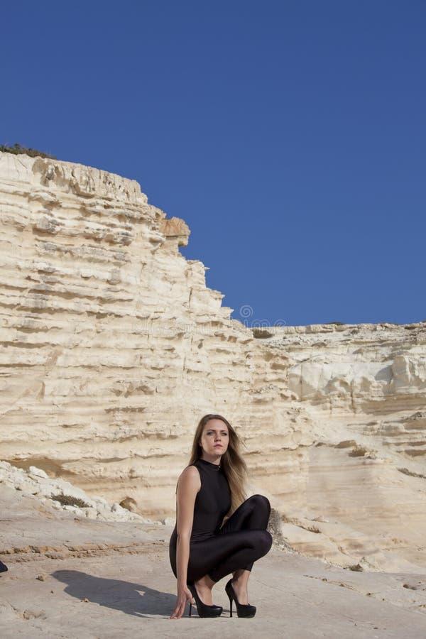 Femme dans la combinaison-pantalon noire sur les roches photographie stock