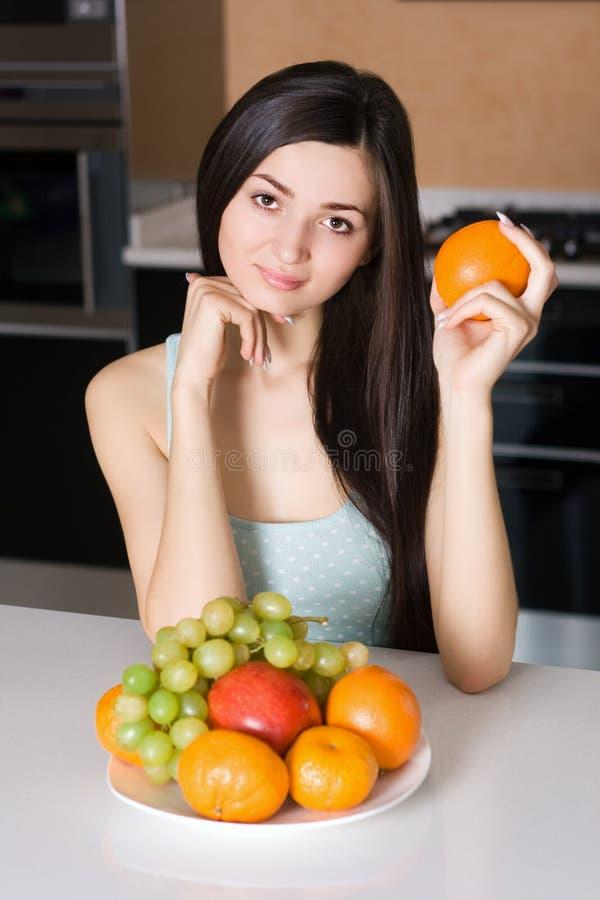 Femme dans la cuisine avec des fruits image libre de droits