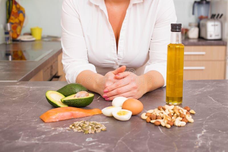 Femme dans la cuisine avec différentes nourritures crues images libres de droits