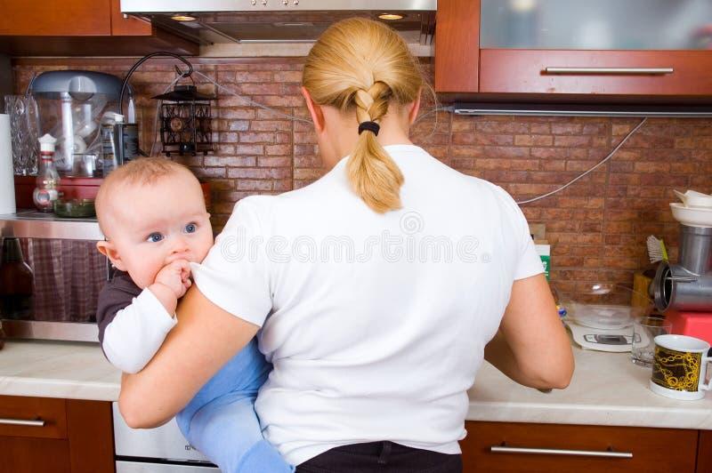 Femme dans la cuisine avec une chéri image stock