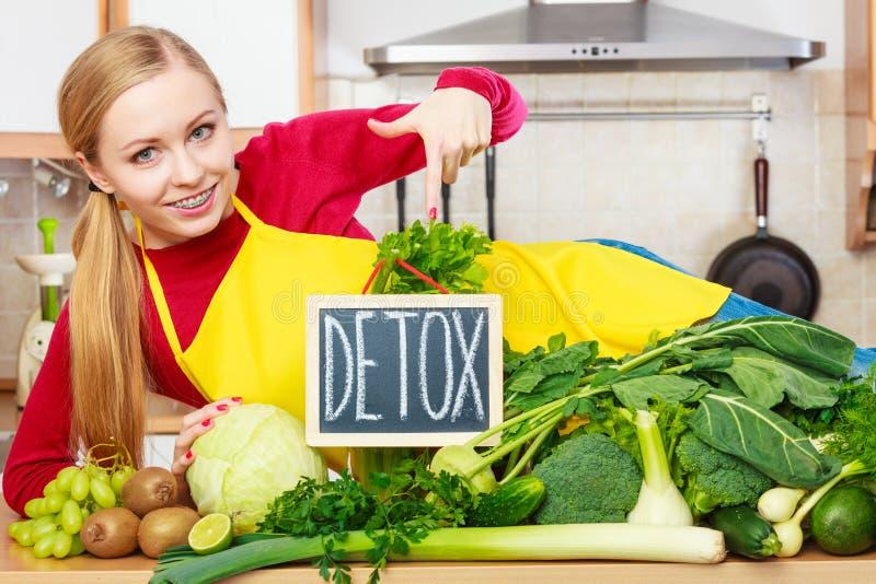 Femme dans la cuisine ayant les légumes verts de régime photographie stock