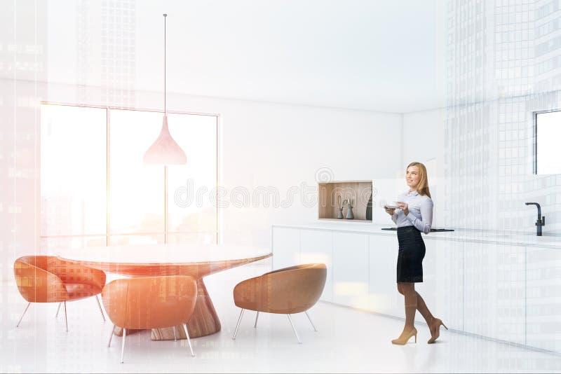 Femme dans la cuisine blanche avec la table ronde photos stock