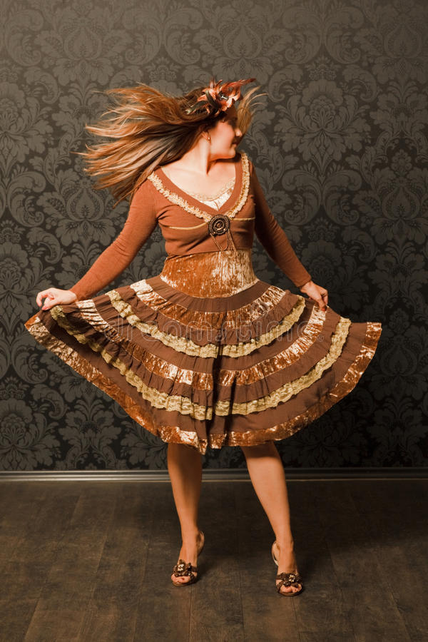 Femme dans la danse brune de robe à côté du mur images stock