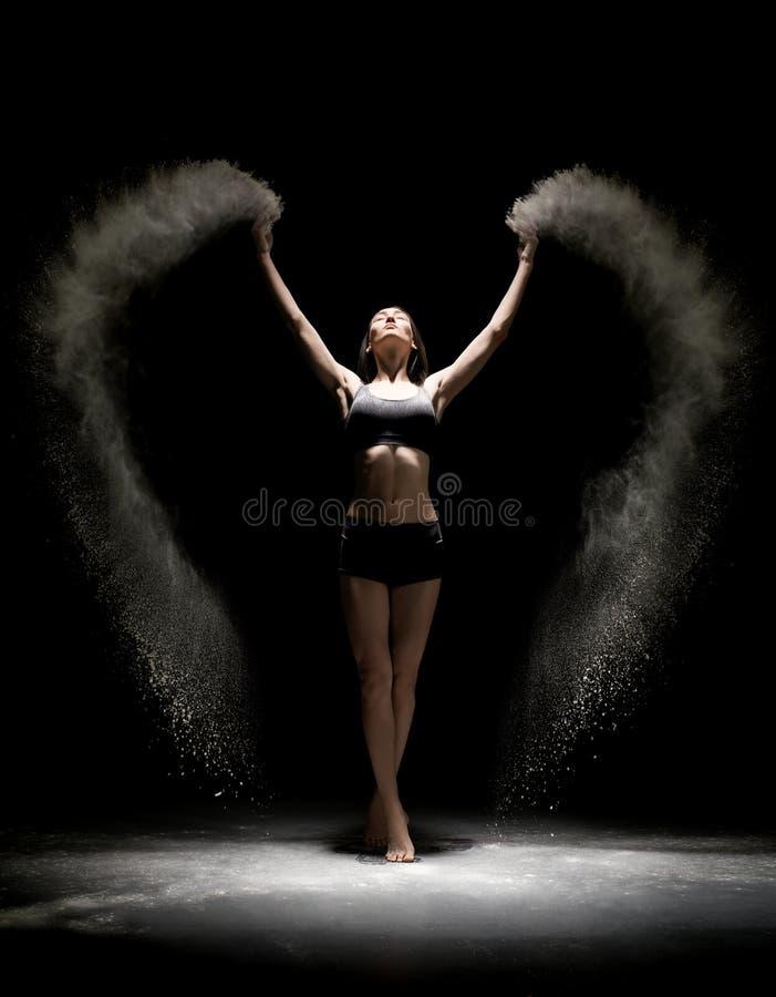 Femme dans la lingerie dansant en poussière dans l'obscurité image stock