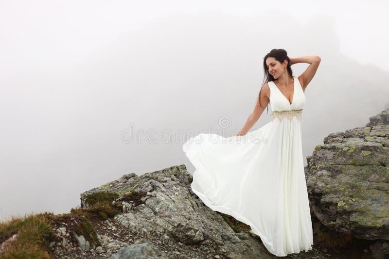 Femme dans la longue robe blanche sur le dessus de montagne photographie stock