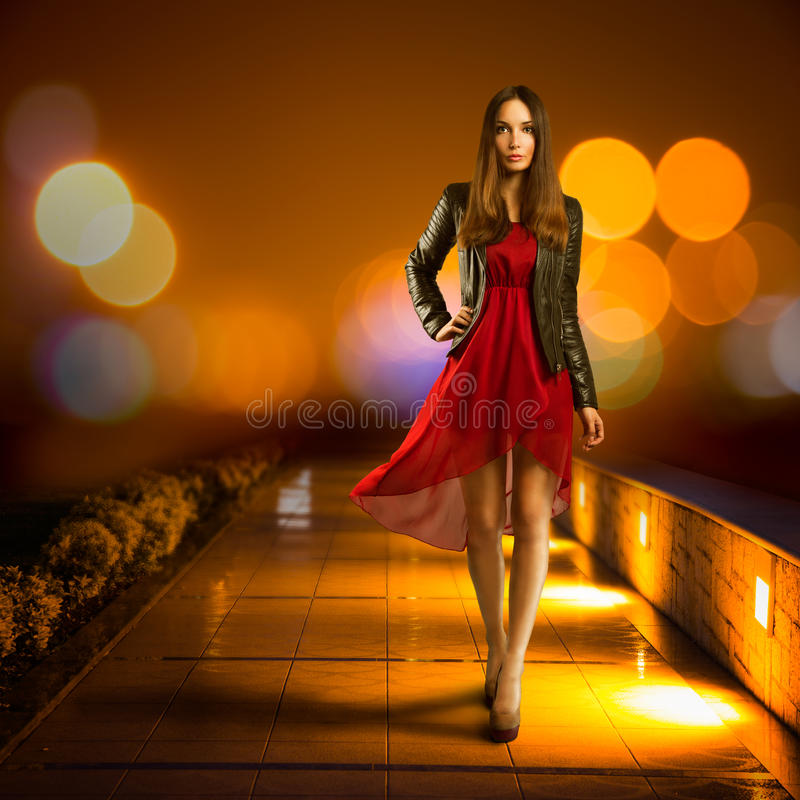 Femme dans la marche rouge de robe Ville de nuit photographie stock