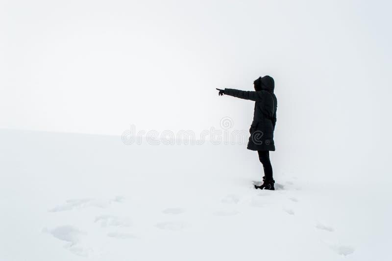 Femme dans la neige dirigeant son doigt vers l'espace vide images libres de droits