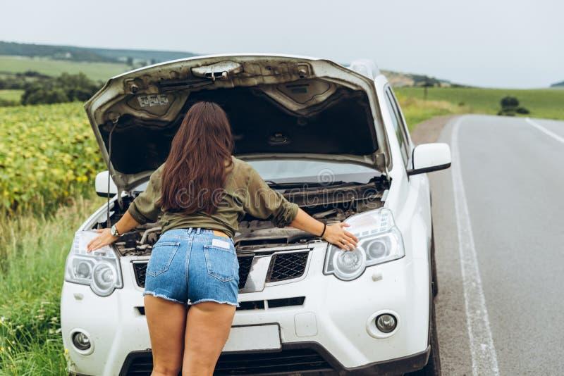 Femme dans la nouvelle voiture cassée de chemises serrées avec le capot ouvert photos libres de droits