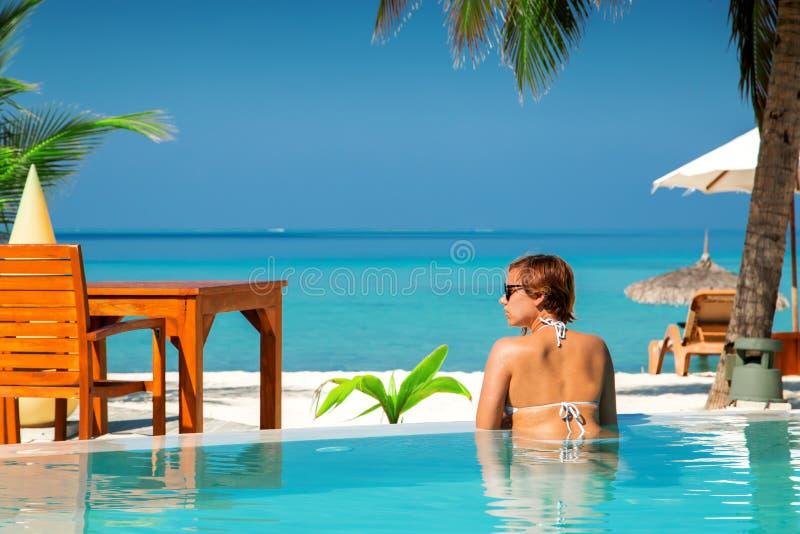 Femme dans la piscine à l'île tropicale photographie stock libre de droits