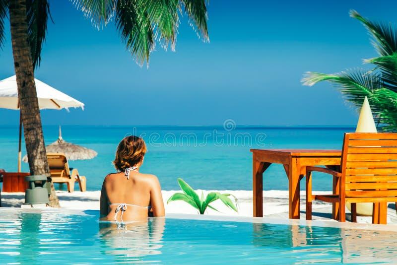 Femme dans la piscine à l'île tropicale image stock