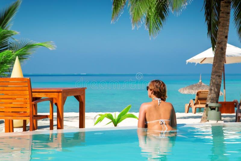 Femme dans la piscine à l'île tropicale images libres de droits