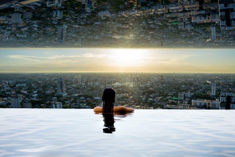 Femme dans la piscine regardant la ville à l'envers photo stock