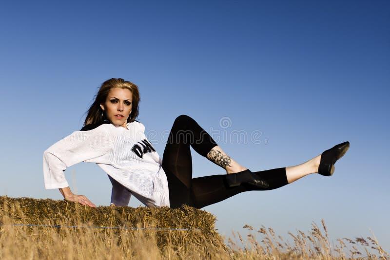 Femme dans la pose de danse se reposant dans un domaine avec le foin image libre de droits
