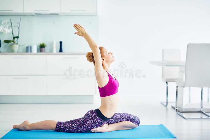 Femme dans la pose de yoga de Kapotasana photographie stock