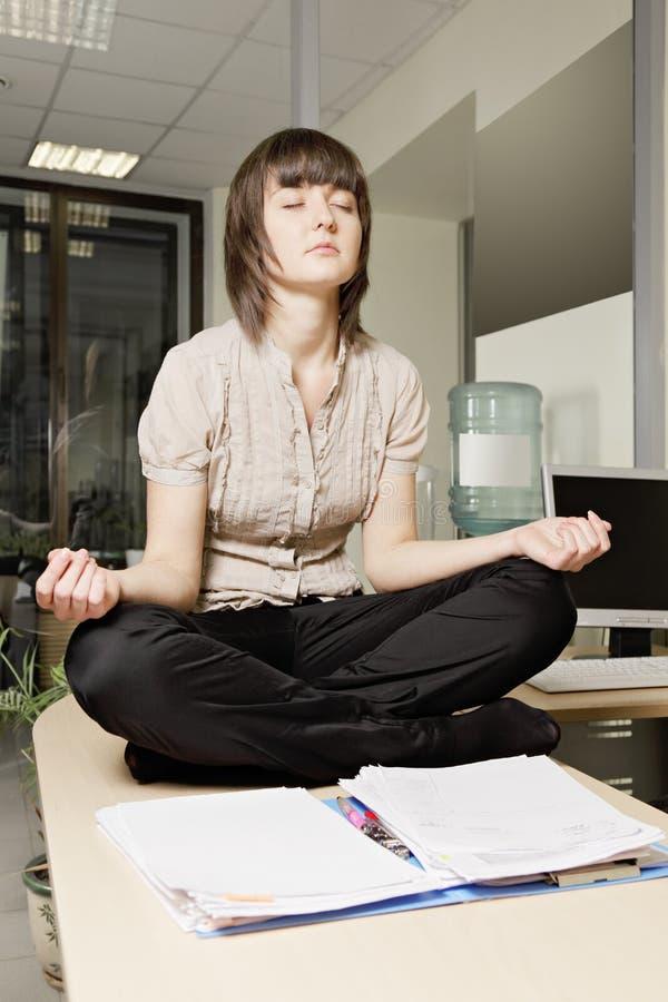 Femme dans la pose de yoga sur le bureau photo libre de droits