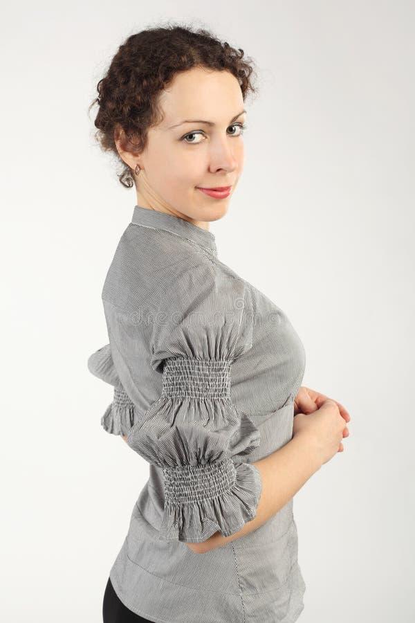 Femme dans la position et le sourire de robe d'affaires image libre de droits