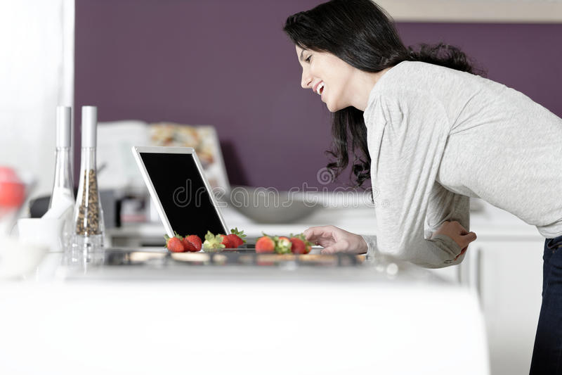 Femme dans la recette de lecture de cuisine photographie stock