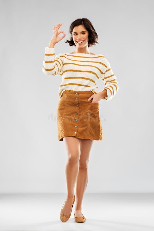 Femme dans la représentation de pull, de jupe et de chaussures correcte photos stock