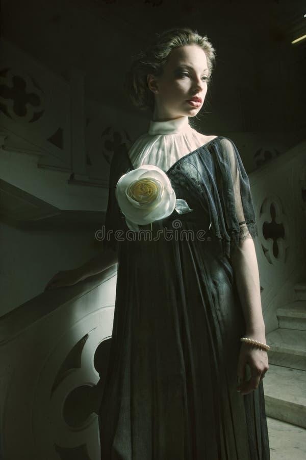Femme dans la robe élégante posant sur des escaliers photo libre de droits