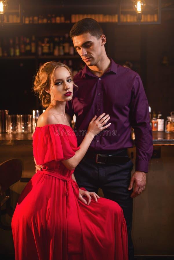 Femme dans la robe avec son homme contre le compteur de barre images stock