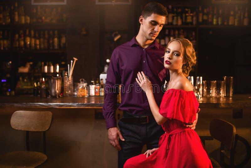 Femme dans la robe avec son homme contre le compteur de barre photographie stock